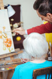 Professional artist teaching elderly woman in painting school Royalty Free Stock Images