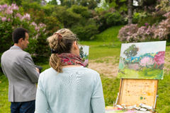 Professional artists evaluating their work in the open air. Professional artists evaluating their glorious work in the open air with background of beautiful Stock Images