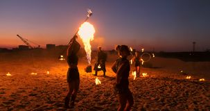 Professional artists show a fire show at a summer festival on the sand in slow motion. Fourth person acrobats from stock video footage