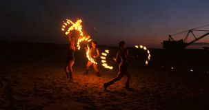 Professional artists show a fire show at a summer festival on the sand in slow motion. Fourth person acrobats from stock footage