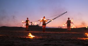 Professional artists show a fire show at a summer festival on the sand in slow motion. Fourth person acrobats from stock video