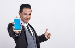 Professional Asian businessman showing a mobile phone and making thumbs up stock image