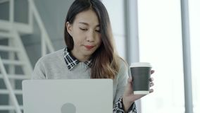 Young Asian female manager using portable computer device and drinking coffee cup while sitting at modern workplace. Professional Asian businesswoman working at stock video footage