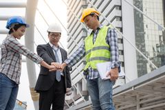 Professional Asian engineering team joining hands together with city background stock photo
