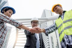 Professional Asian engineering team joining hands together from lower angle view with city background royalty free stock photography