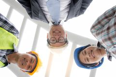 Professional Asian engineering team wearing safety helmet looking at camera from lower angle view royalty free stock photography