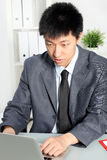 Professional Asian man focusing at his desk Stock Photo