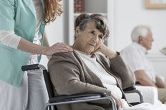 Professional assistant supports senior. Professional assistant supports sad senior on wheelchair during illness Royalty Free Stock Photos