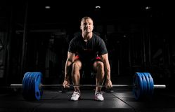 Professional athlete bent over the barbell and is preparing to l. Ift a very heavy weight. Front view Stock Photography