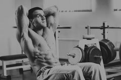 Professional athlete performs exercises in the gym Stock Images