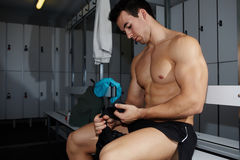Professional athlete removing weight lifting gloves sitting in gym's locker room Royalty Free Stock Photography