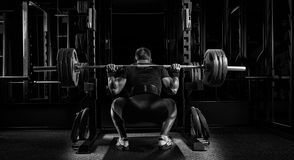 Professional athlete sits with a barbell on his shoulders and pr. Epares to stand with her. View from the back Stock Photo
