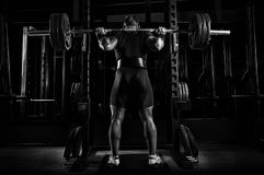 Professional athlete is standing with a barbell on his shoulders. And is about to sit down with her. View from the back Stock Photos