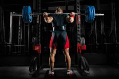 Professional athlete is standing with a barbell on his shoulders. And is about to sit down with her. View from the back Stock Photography