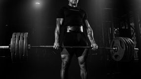 Professional athlete is standing and is holding a very heavy bar. Bell. Front view stock image