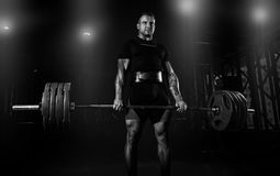 Professional athlete is standing and is holding a very heavy bar. Bell. Front view Royalty Free Stock Photos
