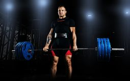 Professional athlete is standing and is holding a very heavy bar. Bell. Front view Stock Images