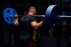 Professional athlete stands with a barbell on his shoulders Royalty Free Stock Image
