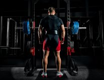 Professional athlete stands in front of the bars with a barbell. And is about to crouch with her. Back view Royalty Free Stock Images