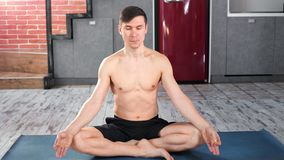 Professional athletic yogi man practicing breathing meditating indoor full shot. Fitness male sitting in lotus position with crossed legs on mat with closed stock video