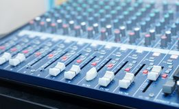 Professional audio mixing console  with knobs, buttons, sliders. Equipment for DJ and music Studio. Focus on fpreground Royalty Free Stock Photography
