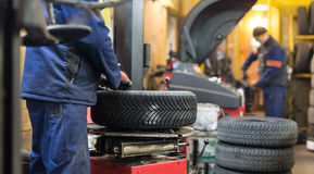 Professional auto mechanic replacing tire on wheel in car repair service. Professional auto mechanic replacing tire on wheel in car repair workshop Stock Photography