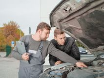Professional auto mechanic showing something in the open hood to client outside. Professional young auto mechanic keeps a notepad and showing something in the stock photo