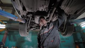 Professional auto mechanic working on the undercarriage of a car in a workshop. He is conducting annual examination with a vehicle stock footage