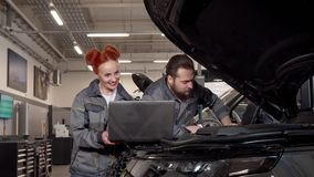 Professional auto mechanics using laptop during car diagnostic at the garage. Bearded repairman talking to his female colleague, examining engine of a modern stock video