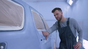Auto painter guy sanding car after paint by hand at paint chamber during repair work at service station stock footage