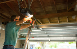 Professional automatic garage door opener repair service technician man working. On a ladder at a home residential location making adjustments and fixing it Royalty Free Stock Photos