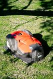 Professional automatic robotic lawnmower. A professional automatic robotic lawnmower on a charging station on green lawn Stock Photography