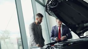 Professional automobile salesman is demonstrating customer car engine under motor hood, men are looking at auto parts