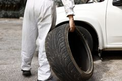 Professional  automotive mechanic in uniform holding tire for fixing car at the garage background. Auto repair service. Stock Image