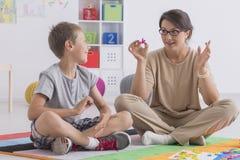 Professional babysitter with a school-boy. Professional babysitter playing educational game with a school-boy Stock Photo