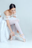 Professional ballerina putting on her ballet shoes Stock Photos