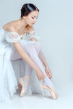 Professional ballerina putting on her ballet shoes. On the gray background royalty free stock photos