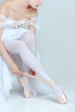 Professional ballerina putting on her ballet shoes. On the gray background royalty free stock images
