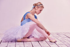 Professional ballerina putting on her ballet shoes. On the wooden floor on a pink background royalty free stock photography