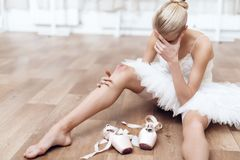 A professional ballerina is sitting on the floor in a dance class. She is dressed in a ballet tutu. She is the professional theater actor. She is tired stock image
