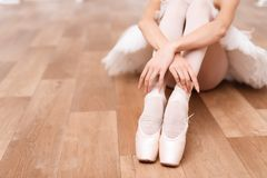 A professional ballerina is sitting on the floor in a dance class. She is dressed in a ballet tutu. She is the professional theater actor. She is tired royalty free stock images