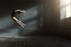 Professional ballet dancer performing in the dark lighted room. Performing jump in the air. Elegant graceful experienced ballet dancer demonstrating her royalty free stock photography