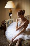 Professional ballet dancer sitting on sofa royalty free stock image