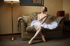 Professional ballet dancer sitting on sofa Stock Photo