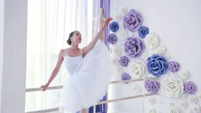 Young ballerina is training ballet element near the barre stand in dance class. Professional ballet dancer in white tutu and pointes is training ballet element royalty free stock image