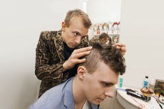 Professional barber examining male customer's in shop Stock Photos