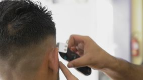 Professional barber giving a trendy haircut to client. A young man in barbershop. Handsome man getting a haircut by a professional barber. Hairdresser works with stock video
