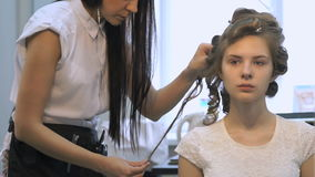 Professional barber makes hairstyle for a girl stock footage