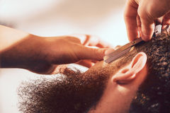 Professional barber shaving beard of his client stock photos
