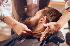 Professional barber shaving beard of his client royalty free stock photos